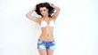 Cute Brunette in Bikini Top and Jeans Shorts Posing Isolated
