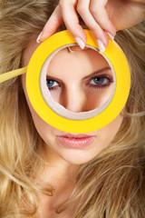 Junge hübsche Frau mit Klebeband gelb gold