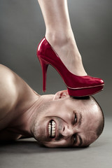 Woman's foot crushing man's head