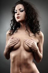Beautiful topless woman covering her breasts
