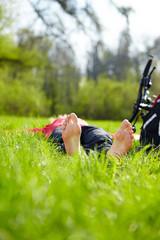 Barefoot tourist enjoying relaxation lying in fresh green grass