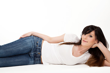 portrait of a beautiful young woman lying on white floor