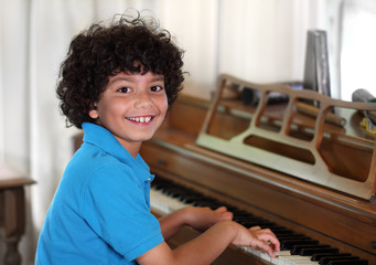 Young mixed race boy smiles while playing the piano