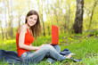 Beautiful girl sitting on the grass with a notebook
