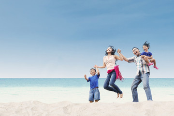 Cheerful family jumping at beach