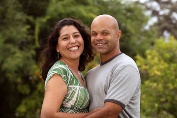 A happy mixed race couple relax outside