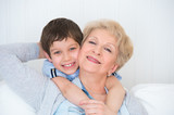 Lovely little boy with his grandmother having fun and happy mome