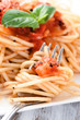 Close up of bite of pasta with red sauce on a fork