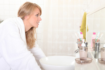 Woman looking into bathroom mirror