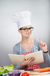 Smiling woman with cookbook raising index finger up