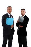 two businessmen holding folders