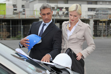 Male and female architects stood by car