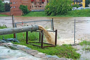 impressive exhaust flows into river rainwater and mud