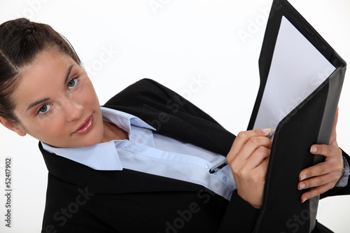 Businesswoman writing in a folder