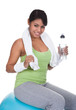 Woman Sitting On Pilates Ball Holding Water Bottle