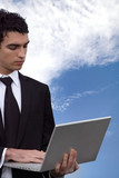 young business man doing computer outside