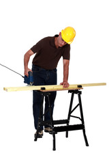 Carpenter sawing a plank