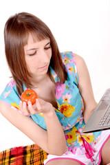 девушка в летней одежде с ноутбуком и помидором