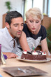 Couple blowing birthday candle