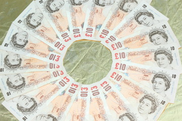English £10 notes in a circle on a gold background