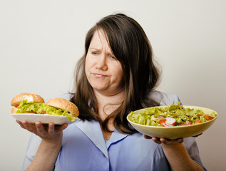 fat white woman having choise between hamburger and salad