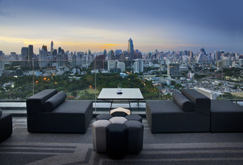Sofa on terrace overlooking park and building,Bangkok