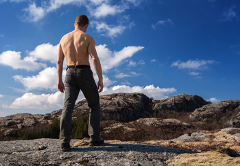 Topless strong man stands on the mountain