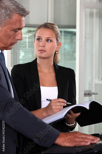 handsome middle-aged businessman with young blonde secretary