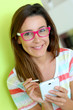 Brunette girl with eyeglasses using smartphone