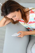 Young woman using smartphone sitting in sofa
