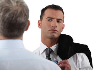 Man looking suspiciously at his colleague