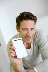 Man showing smartphone to camera