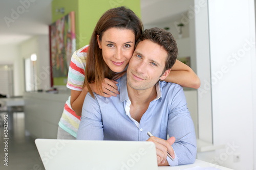 Couple at home looking at bank account on internet