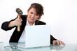 Woman smashing laptop with hammer