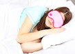 Beautiful young woman sleeping in bed with eye mask