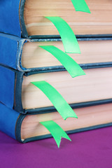Many books with bookmarks on purple background
