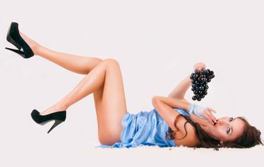 сексуальная девушка в ночной рубашке кушает виноград