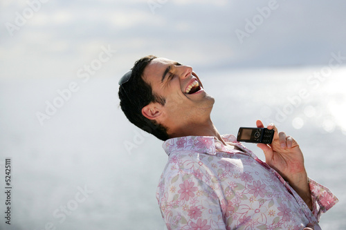 Man laughing by the water's edge