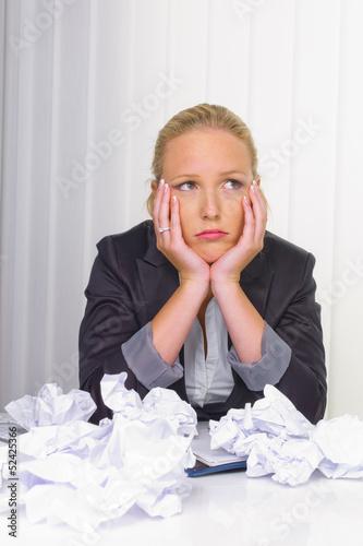 Frau im Büro mit zerknülltem Papier
