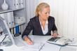 Frau im Büro mit Rechenmaschine