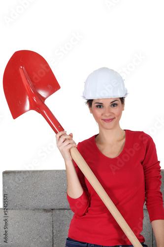 sexy craftswoman holding a shovel