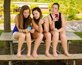 pre-teen girls texting while hanging out at their school