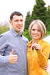 Portrait of happy beautiful couple with car key, standing near