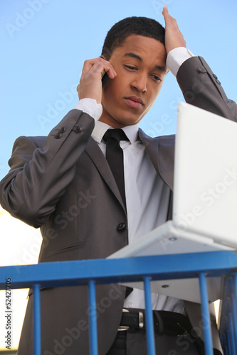 Stressed young businessman with laptop