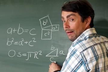 Lehrer mit Formel an Tafel zeigt Schülern Geometr