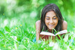 dark-haired young woman reading red book
