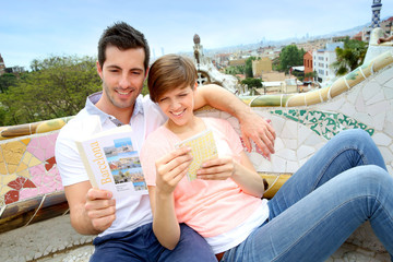 Tourists reading travel book in Guell Park, Barcelona