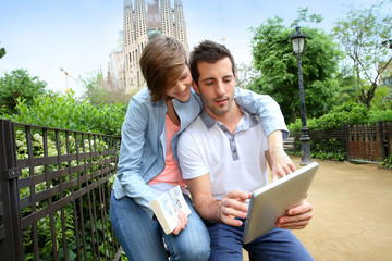 Couple of tourists using tablet in Barcelona