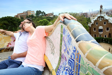 Couple of tourists relaxing on Guell Park bench