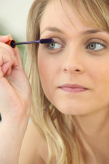 a woman putting mascara